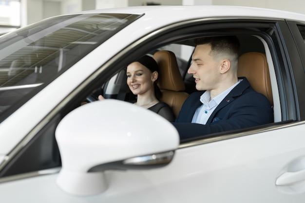 Супружеская пара муж и жена сидят в машине в автосалоне Premium Фотографии
