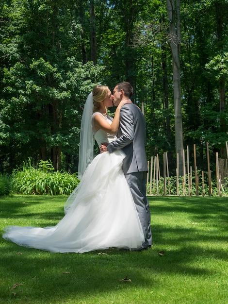 Супружеская пара целуется в саду в окружении зелени под солнечным светом Бесплатные Фотографии