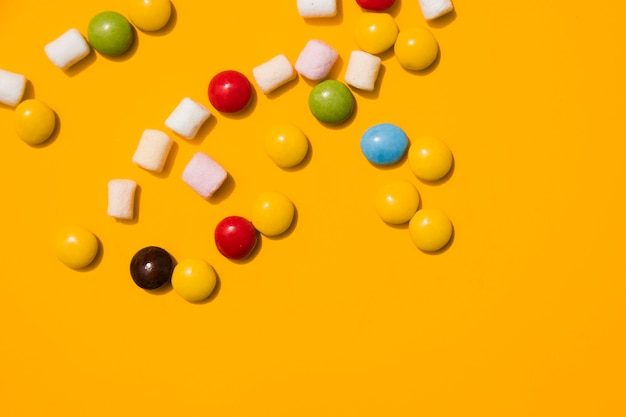Marshmallow and colorful candies on yellow background Free Photo