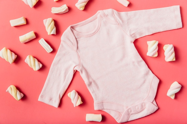 Marshmallow surrounded with pink baby onesie on peach background Free Photo