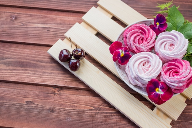 Marshmallow with cherry berry and flowers on light wooden background Premium Photo
