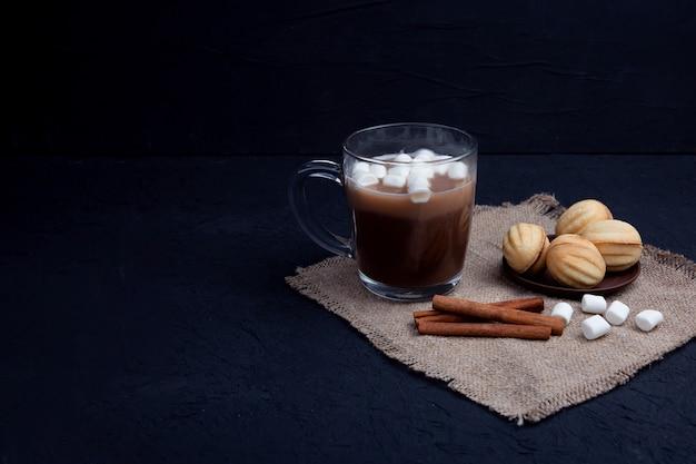 マシュマロは、ホットチョコレートココアドリンクと一緒にガラスのマグカップに落ちます。冬の食べ物や飲み物のコンセプト。 Premium写真