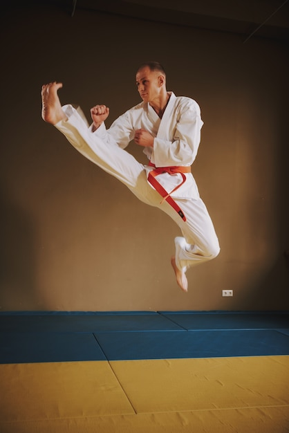 Martial arts fighter in white jumping with kick Premium Photo