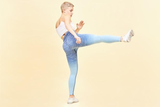 Concetto di arti marziali, karate e kung fu. immagine a figura intera di combattente mma giovane donna bionda e tenace in top, leggings e scarpe da ginnastica che si allena al chiuso che calcia il nemico invisibile con una gamba tesa Foto Gratuite