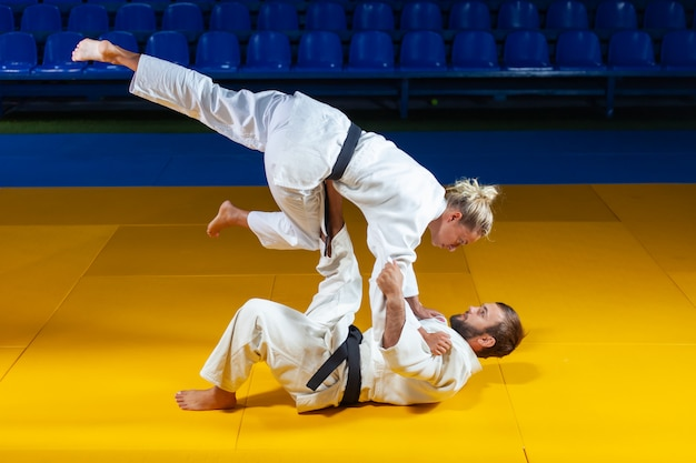 Martial arts. sparing portners. sport man and woman in white kimono train judo throws and captures in the sports hall Premium Photo