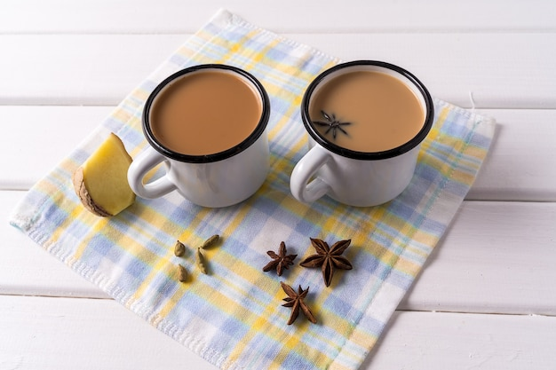 Masala chai tea in aluminum mugs, anise spice on white table. Premium Photo