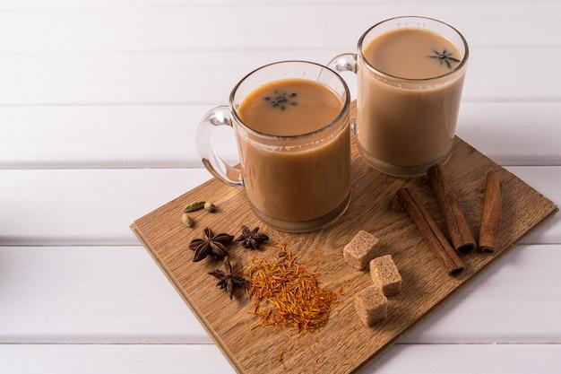 Masala chai tea in mugs, brown sugar, cinnamon sticks, anise and badian over white table background. Premium Photo