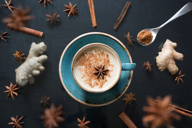 Masala indian tea in cup with levitation spices and cinnamon on black. Premium Photo