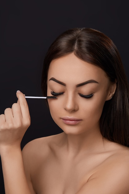 Mascara, beauty makeup, fresh soft skin and long black thick eyelashes applying mascara with cosmetic brush, eyelashes extensions, fake eyelashes, Premium Photo