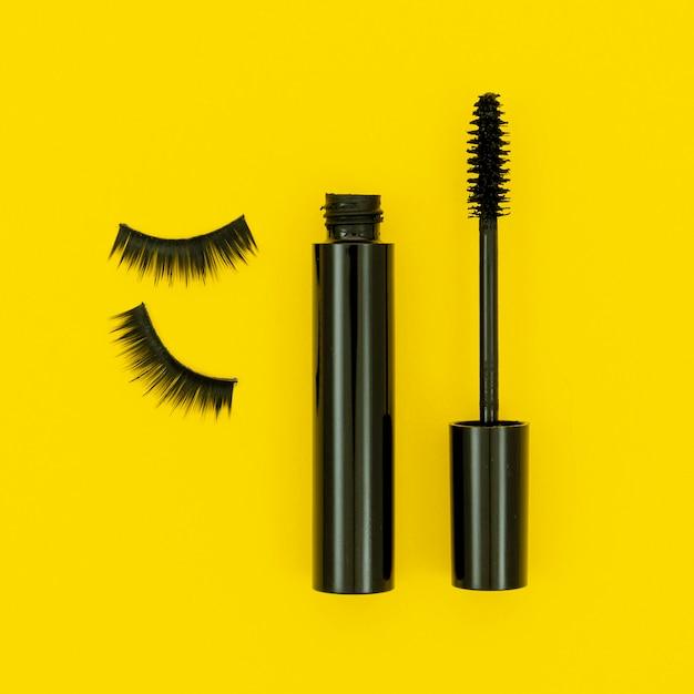 Mascara and fake lashes on yellow background Free Photo