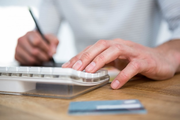 Masculine hands taking notes and typing on keyboard in a bright office Premium Photo