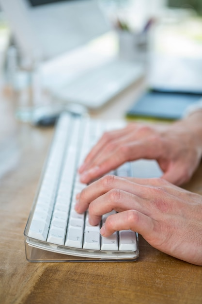 Masculine hands typing on keyboard in a bright office Premium Photo