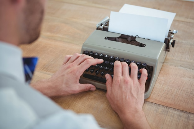 Masculine hands typing on old typewriter on wooden table Premium Photo