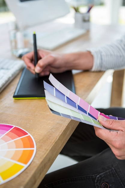 Masculine hands writing on digital tablet about color samples in a bright office Premium Photo