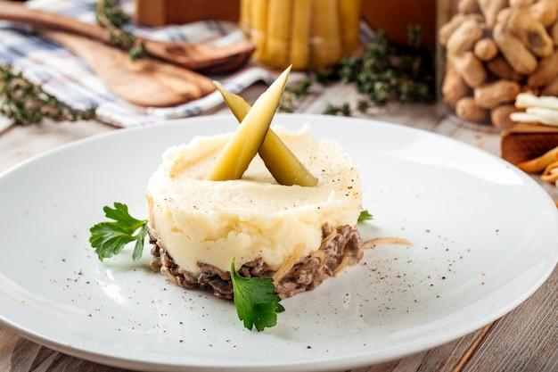 Картофельное пюре с говядиной в сливочном соусе и солеными огурцами Premium Фотографии