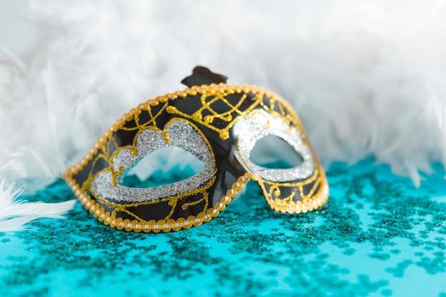 Mask on confetti near feathers Free Photo
