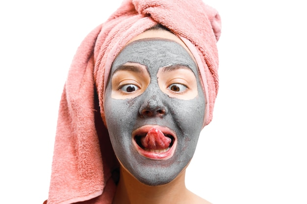 肌の女性のためのマスク、女の子は彼女の舌を出し、女の子は味にフェイスマスクを試みます Premium写真