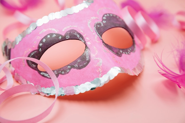 Mask near ornament quills and tape Free Photo