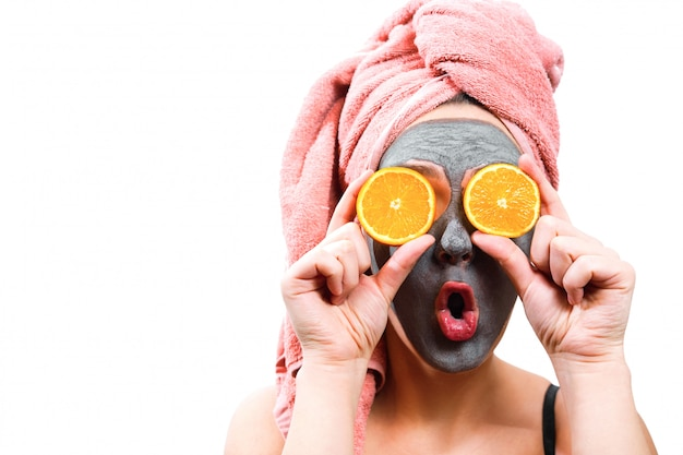 Mask for skin woman, happy and funny girl makes mask for face skin, girl closes her eyes with orange, isolated photo, emotional gender role Premium Photo