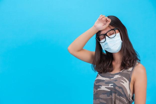 La ragazza mascherata mostra la sua mano con la fronte chiusa su una parete blu. Foto Gratuite