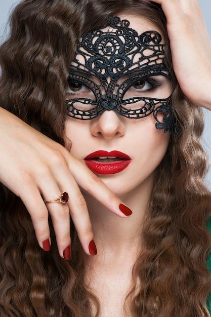 Женщина красоты модельная нося венецианскую маску масленицы masquerade на партии над предпосылкой праздника темной с волшебными звездами. Premium Фотографии