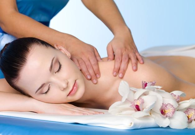 Массаж плеча для молодой красивой женщины в спа салоне - горизонтальный Бесплатные Фотографии
