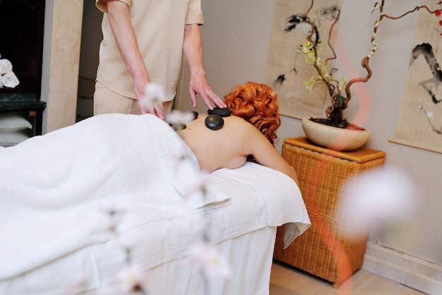The massage stones on the body of a red-haired young girl. stone therapy Premium Photo