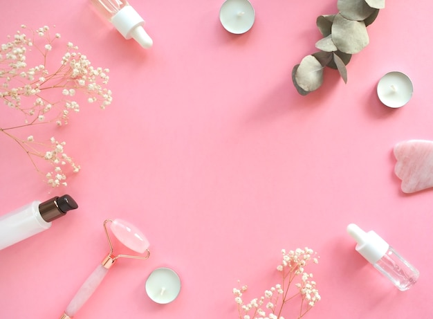ピンクの天然翡翠で顔をクォーツローラーでマッサージします。美容美容液入りのガッシュマッサージツール。アンチエイジングと自宅でのリフティング。フェイシャルケアマッサージとリラクゼーションのコンセプト。 Premium写真