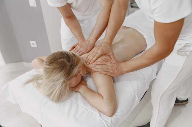Il massaggio a quattro mani. concetto di assistenza sanitaria e bellezza femminile. due massaggiatrici fanno un doppio massaggio di una ragazza. la donna in un salone spa. Foto Gratuite