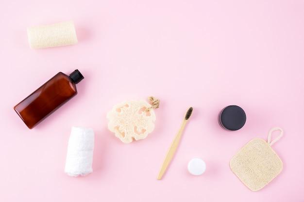 マッサージャー、クリーム、ボトル、ヘチマスポンジスクラブスポンジ、ピンクの表面に竹の歯ブラシ Premium写真