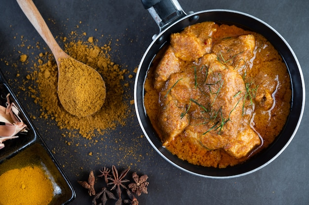 Massaman curry in a frying pan with spices on the cement floor Free Photo