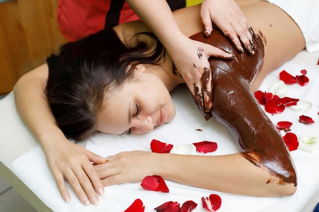 Masseur applying chocolate to woman's back Premium Photo