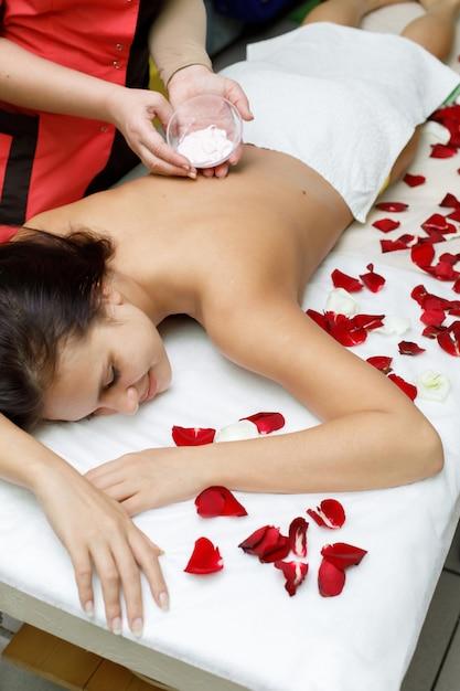 Masseur applying cream to woman's back Premium Photo