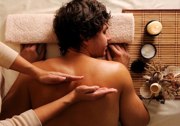 Il massaggiatore fa un massaggio alla schiena al ragazzo in un salone di bellezza Foto Gratuite