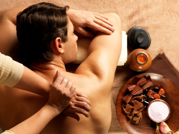 Massaggiatore che fa massaggio della spina dorsale sul corpo dell'uomo nel salone della stazione termale. concetto di trattamento di bellezza. Foto Gratuite