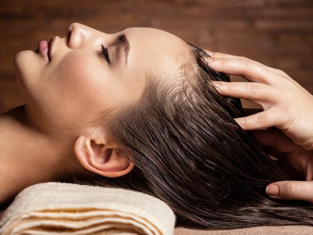 Massaggiatore che fa massaggiare la testa e i capelli per una donna nel salone della stazione termale Foto Gratuite