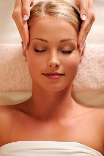 Massaggiatore che fa massaggiare le tempie per la giovane bella donna - vista dall'alto Foto Gratuite