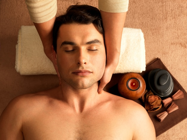 Masseur doing neck massage on man in the spa salon. Free Photo