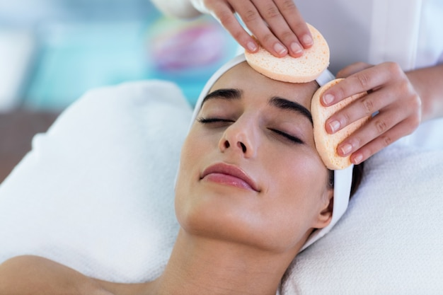 Masseuse cleaning woman face with cotton swabs Premium Photo