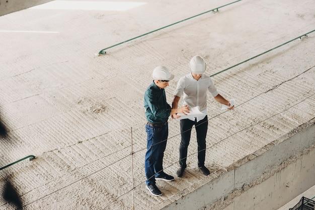 마스터와 건축가는 작업 진행 상황을 조사하면서 건물의 평면도를 조사합니다. 프리미엄 사진