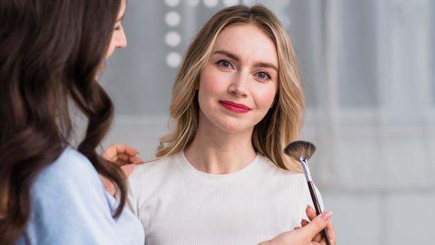 Master applying makeup to smiling blond woman Free Photo