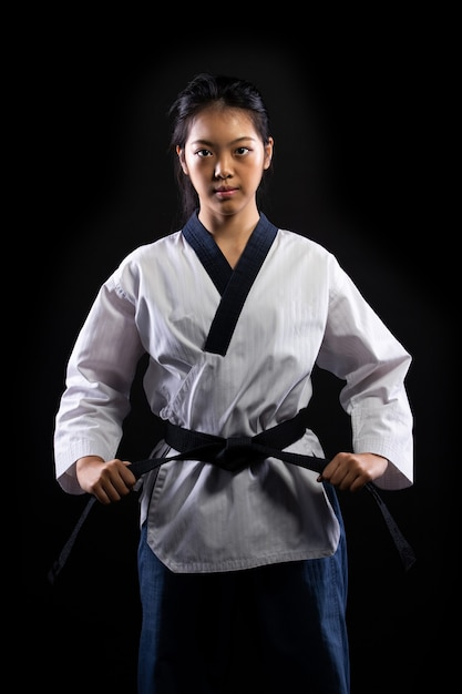 Master black belt taekwondo karate girl who is national athlete young teenager show traditional fighting poses punch in sport uniform dress, black wall isolated, motion blur on foots hands Premium Photo