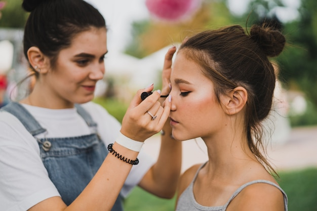 Master class make-up. girl makes make-up to her friend Free Photo