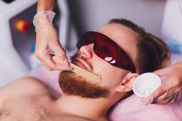 Master doctor performs procedure of removing permanently unwanted facial hair in bearded man with laser. beauty and health. Premium Photo