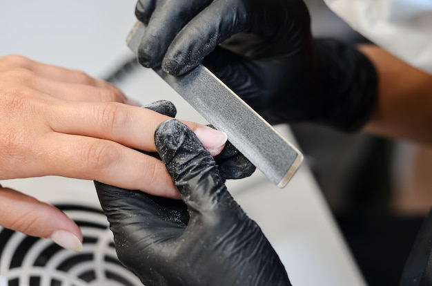 The master does hardware manicure in the beauty salon Premium Photo