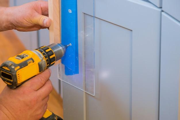 Master drills the cabinet door in the cabinet door Premium Photo
