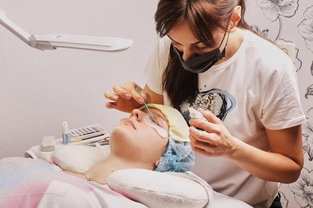 Master eyelash extension at work, apply glue, home workplace Premium Photo