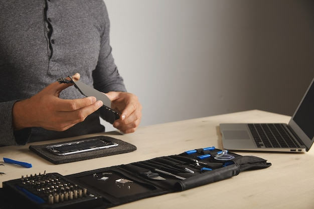 Master holds new screen for replacement above disassembled smartphone in his laboratory, tool kit with instruments and laptop in front of him on white table, space for your text on right Free Photo