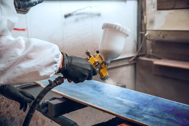 Maestro pittore in una fabbrica - pittura industriale del legno con pistola a spruzzo. Foto Gratuite