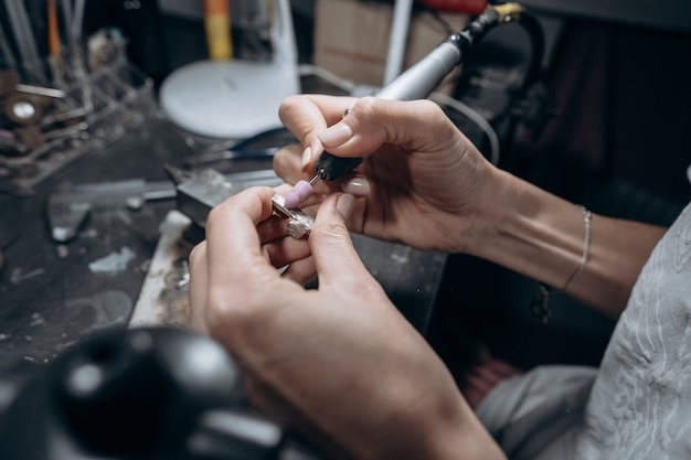 The master processes the valuable metal in the home workshop Free Photo